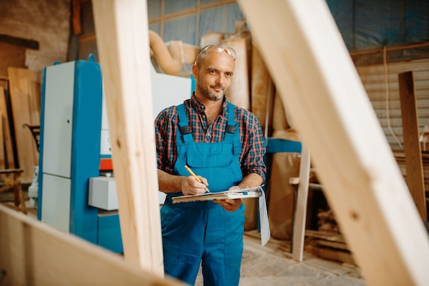 Carpenter with notebook, woodworking, lumber industry, carpentry.
