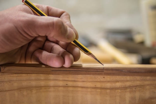 Carpenter with a pencil marks the workpiece