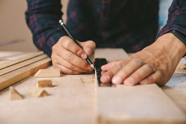 Carpenter with a pencil and ruler mark on wooden board on table. construction industry, housework do it yourself.