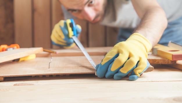 木の板を測定する定規を持つ大工。