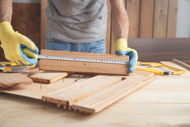木の板を測定する定規を持つ大工