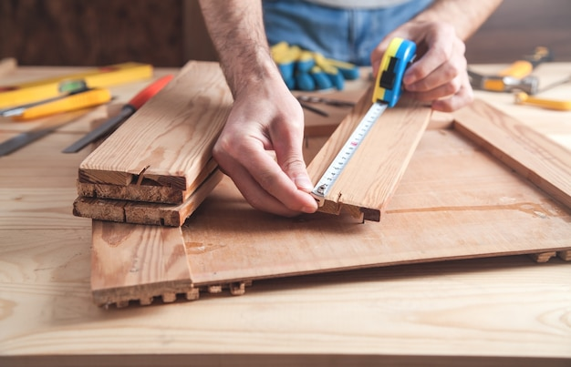 Carpenter with ruler measuring wood plank.