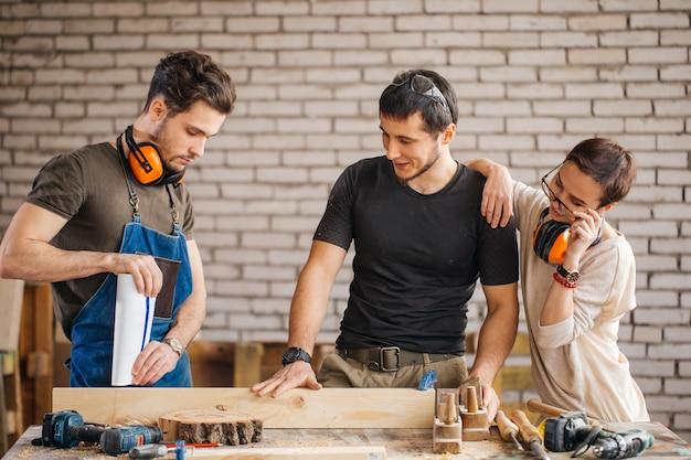 Плотник со студентами в деревообрабатывающей мастерской