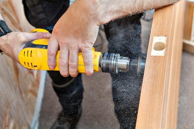 黄色のドリルで大工が木製の内部ドアに大きな穴のロックを開けました。