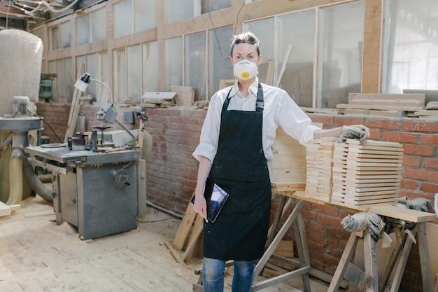 彼女自身のウッドショップで大工の女性の肖像画