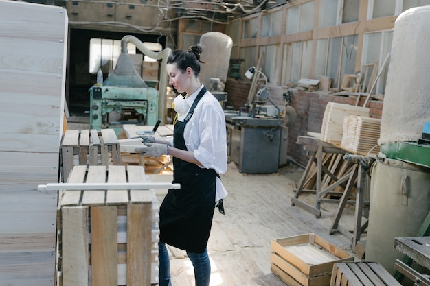 Портрет женщины плотника в ее собственной столярной мастерской