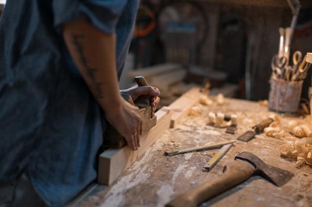Женщина-плотник работает в мастерской с деревом. мастер стиля жизни
