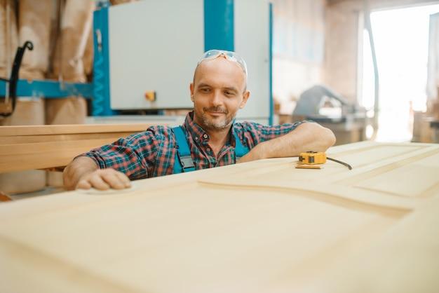 Carpenter, wooden door manufacturing, woodworking, lumber industry, carpentry.