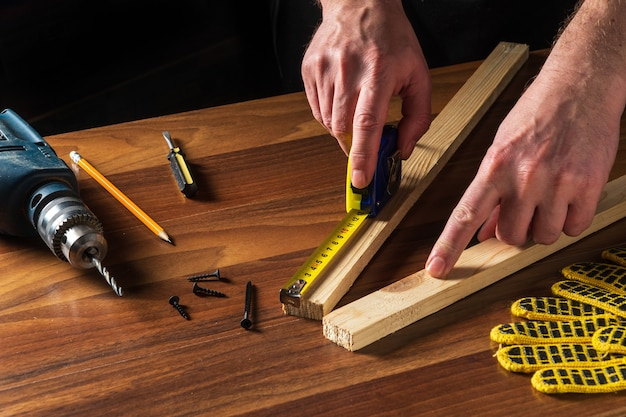 Carpenter or woodworker uses a construction tape to measure the length of a piece of wood. hands of the master close-up at work.