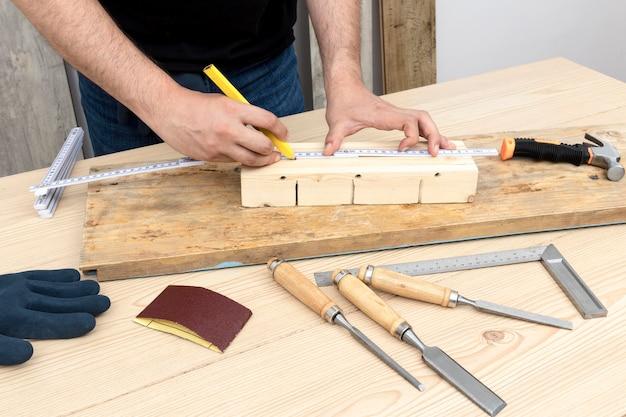 彼のワークショップで木材から家の装飾を作成する大工労働者