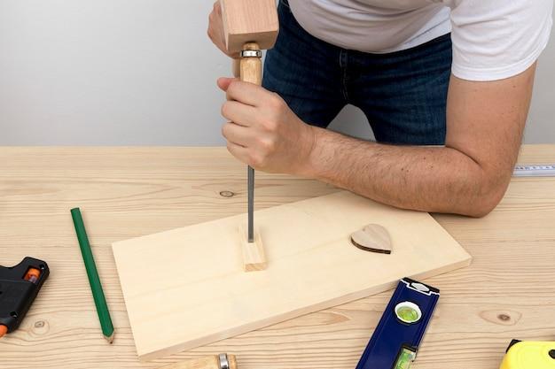 Плотник создает украшение для дома из дерева в своей мастерской