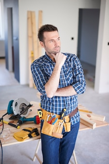 Carpenter working in a house and thinking
