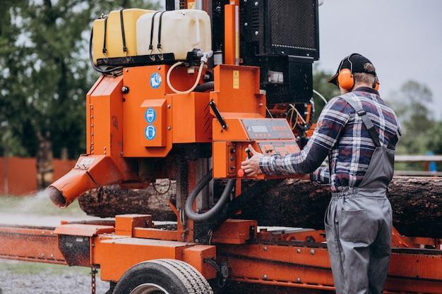 Плотник работает на лесопилке на деревообрабатывающей промышленности
