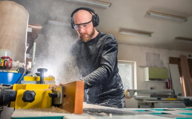 大工仕事場、産業コンセプトで木工のこぎり機で働く大工