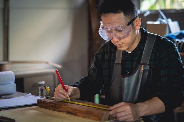 大工店で木に取り組んでいる大工。男は大工屋で働いています