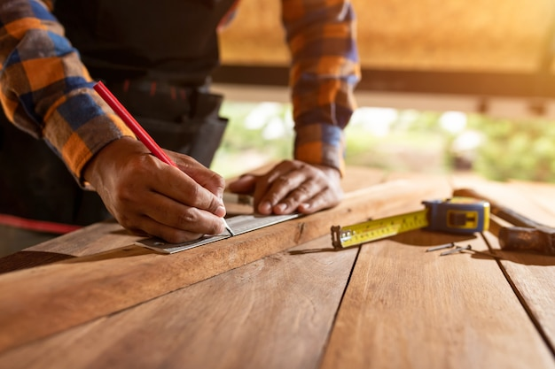 Плотник работает на деревообрабатывающих станках в столярной мастерской. человек работает в столярной мастерской с использованием защитных наушников концепции безопасности прежде всего.