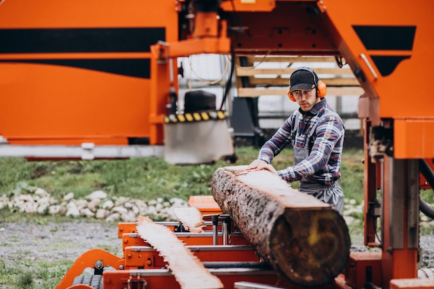 Carpenter working on a sawmill on a wood manufacture