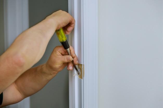 ロックに穴の開いた木製のドアを備えたのみを使用して働く大工がドアを取り付けています