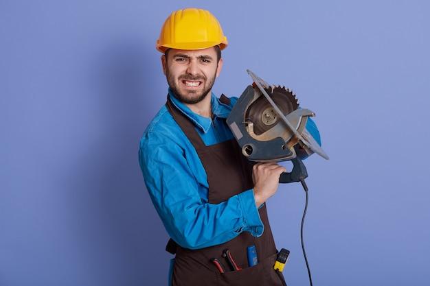 Плотник работает с циркулярной пилой, глядя прямо в камеру с сердитым выражением лица, в желтом шлеме и коричневом фартуке
