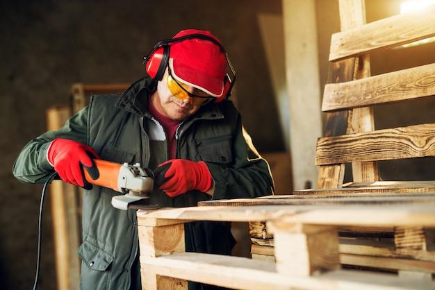 大工はプロの制服で電動グラインダーツールを使用します。