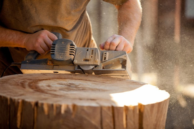 Carpenter working with electric planer on wooden stump outdoors