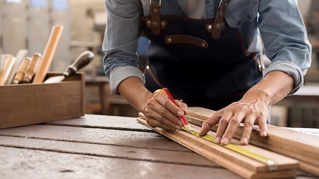 목공 상점에서 나무 테이블에 장비를 사용하는 목수. 여자는 목공 상점에서 작동합니다.