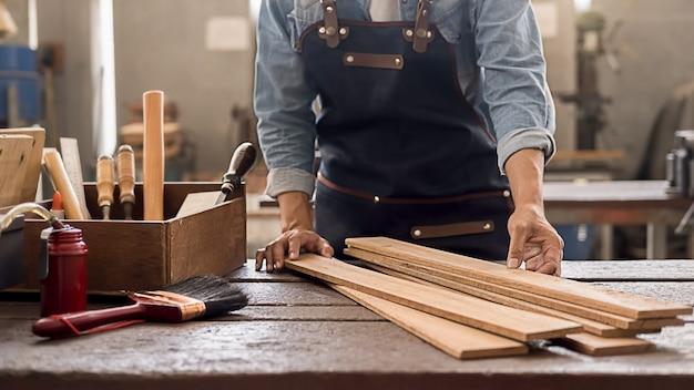 Плотник работает с оборудованием на деревянном столе в столярной мастерской.