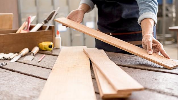 목공 상점에서 나무 테이블에 장비를 사용하는 목수.
