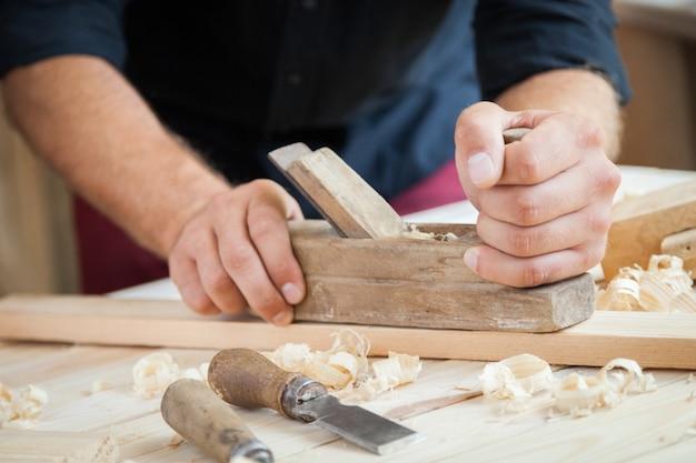 Плотник работает с самолетом на деревянном фоне