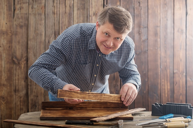 Carpenter working with tools on wooden wall