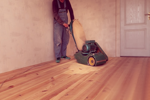 Carpenter works by electric grinding wood machine in a room
