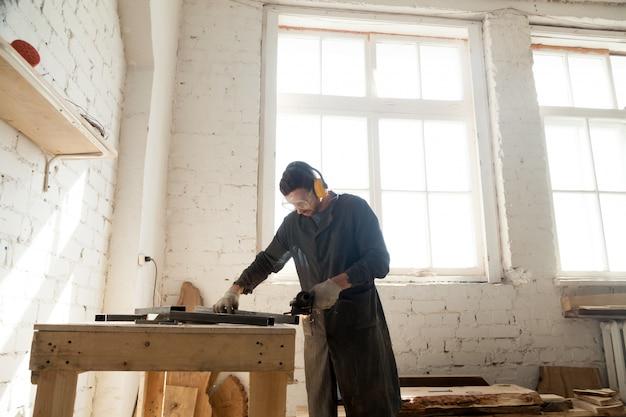 Carpenter works in custom furniture manufacturing