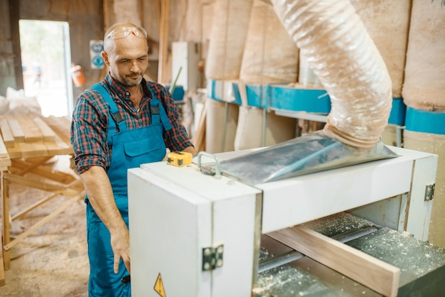 Carpenter works on plane machine, woodworking, lumber industry, carpentry. wood processing on furniture factory