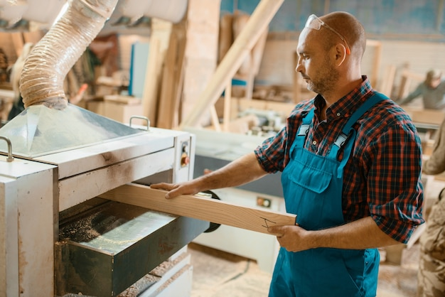 Carpenter works on plane machine, woodworking, lumber industry, carpentry.