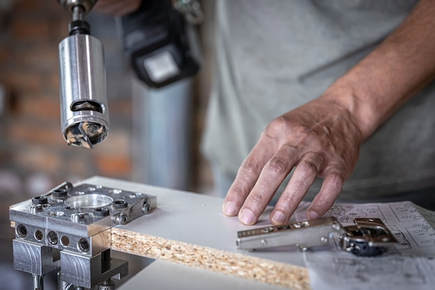 The carpenter works with a professional precision drilling tool.