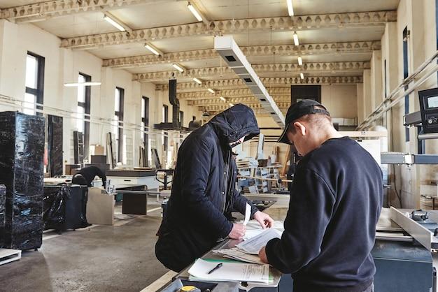 Плотники занимаются бумагами в столярной мастерской. горизонтальный снимок