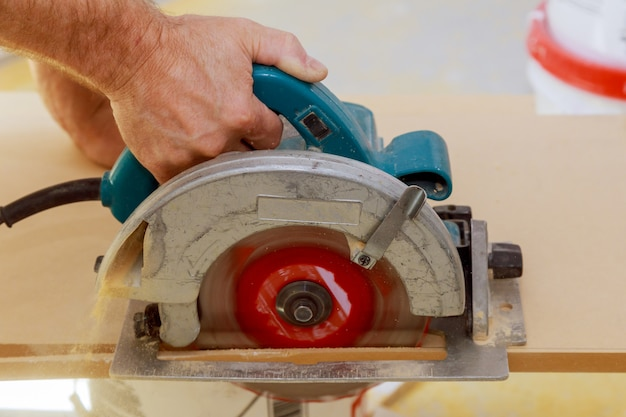 Carpenters hands cutting wood with electric saw