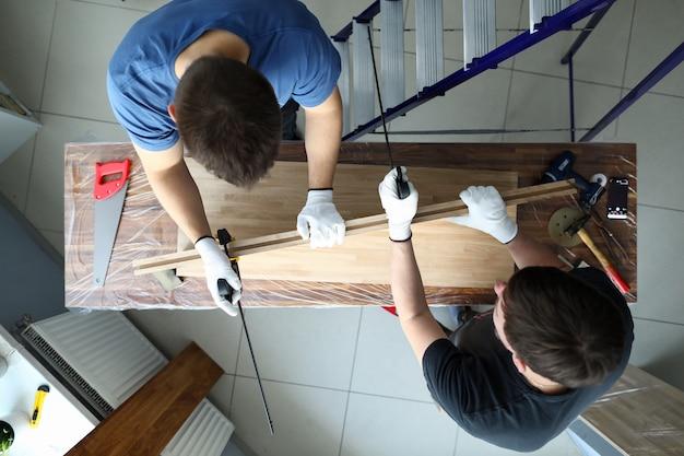 Плотники измеряют деревянное полотно рулеткой. доски обрабатываются на верстаке и собираются отдельные элементы. маркировка деревянных деталей и их обработка. натуральный рисунок и окраска дерева