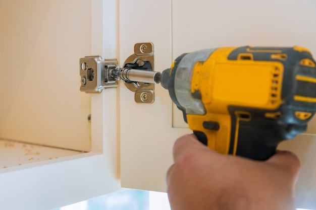 Carpentry assembly of furniture accessories in the kitchen door with hinge to a kitchen cabinet a screwdriver.