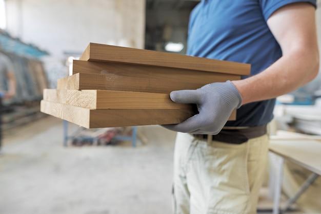 Плотницкая мастерская по изготовлению деревянной мебели. деревянные детали в руках плотника-мужчины