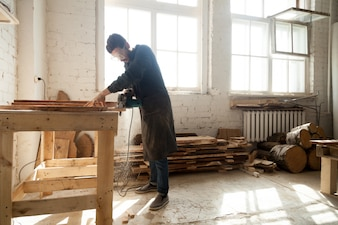 Carpentry workshop. Man using electric hand saw on wooden planks