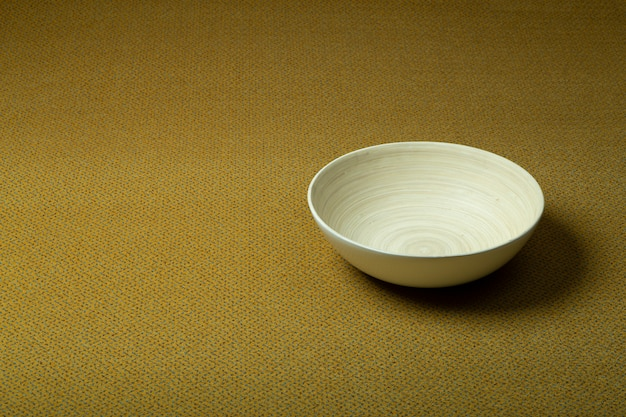 背景の床のカーペット。木製ボウルと同じ色の黄色のカーペット。インテリアデザインと制作。
