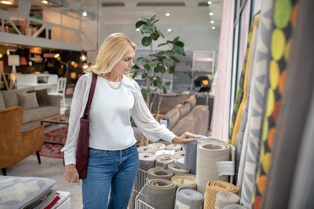 Ковры и коврики. серьезная женщина в мебельном магазине стоит напротив ковров с интересом смотрит, рука на ковре.