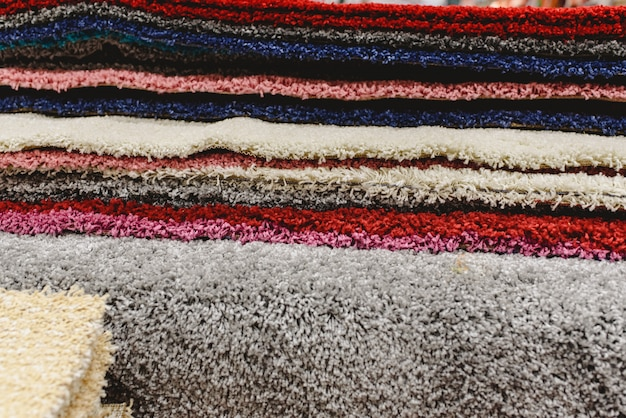 Carpets of various colors stacked in a warehouse.