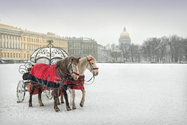 Карета с двумя лошадьми на заснеженной дворцовой площади в санкт-петербурге и исаакиевский собор вдали