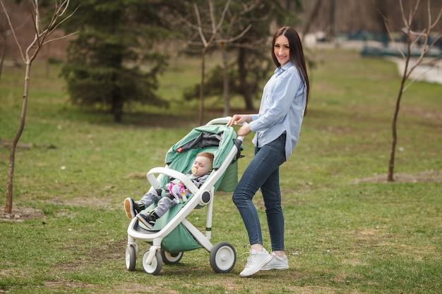 Carriegeで彼女の子供と歩く若い陽気な母