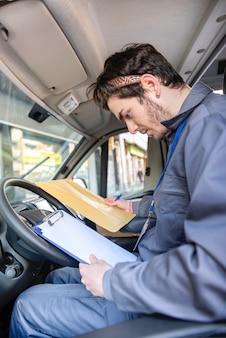 注文を配達するためにパッケージを見て運転席に制服を着たキャリア