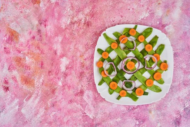 白い皿にニンジンと豆。