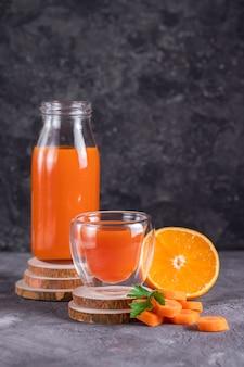 Морковный и апельсиновый сок в бутылке и стакане на деревянных подставках в сдержанном ключе