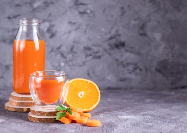 Морковный и апельсиновый сок в бутылке и стакане на деревянных подставках